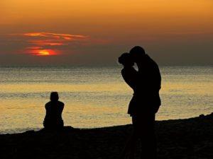 Eifersucht in der Beziehung - zu sehen sind ein Mann eine Frau, die sich küssen und eine andere frau, die allein und eifersücht im Hintergrund sitzt