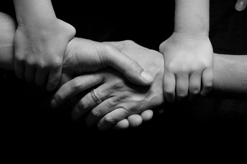 Hände, die sich festhalten und somit Vertrauen in der Beziehung symbolisieren