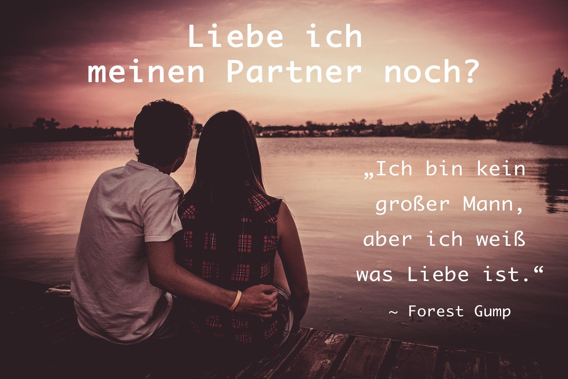 Paar sitzt und schaut den Sonnenuntergang an als Symbolik für die Frage: Liebe ich meinen Partner noch?